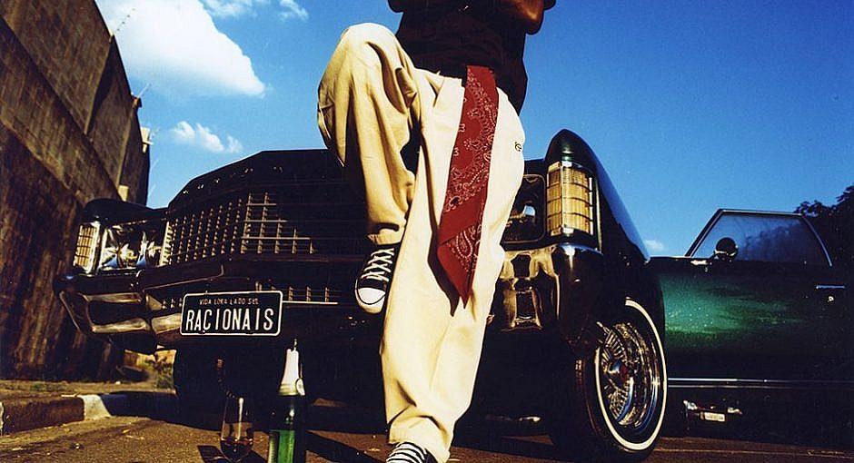 Capa do álbum do Racionais MC's: um homem apoiado num carro com a placa Racionais, de all-star e uma bandana vermelha pendurada na calça
