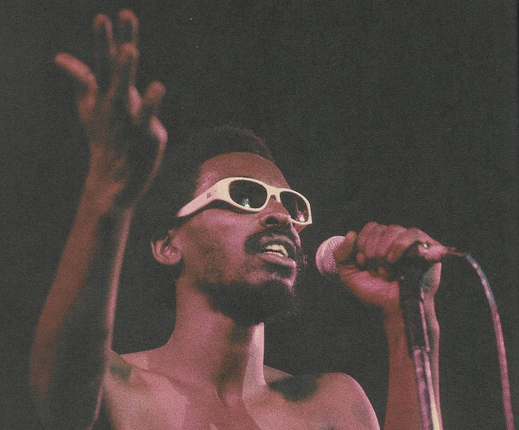 foto de Itamar Assumpção, a mão direita erguida, a esquerda no microfone. Está de barba, sem camisa e um óculos de armação branca