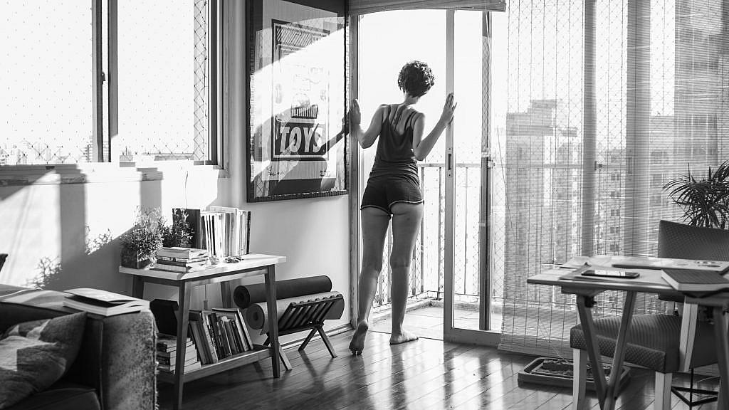 """Fotografia em preto e branco onde apareço de costas abrindo a porta de vidro da varanda do meu apartamento, olhando para fora. Estou descalça, com roupas simples, shorts e cabelo curtos. O pé esquerdo levemente levantando, a sola suja. Ao redor, os móveis da casa, uma mesa de trabalho, outra cheia de livros, os tapetes de yoga enrolados em um canto, o braço do sofá arranhado pelos gatos, um quadro na parede com um grafite onde se lê """"toys"""". A luz invade a sala na diagonal, indicando que é fim de tarde."""