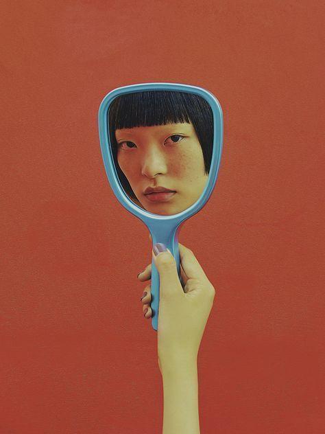 fotografia de uma mulher segurando um espelho retrô, de cabo azul,  frente de uma parede cor de vinho. No reflexo do espelho, aparece o rosto de uma mulher chinesa, com a franja cortada bem reta.
