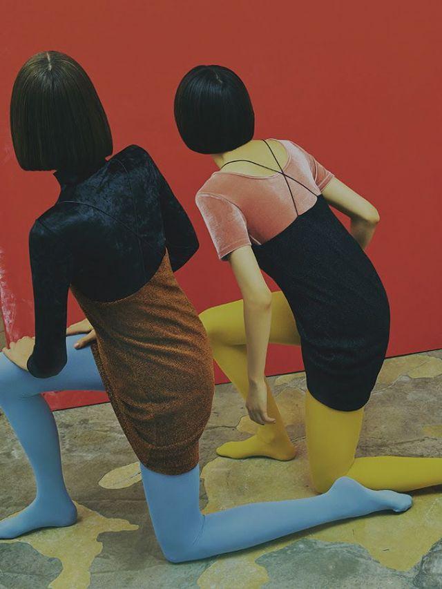 Fotografia de duas mulheres fazendo o mesmo movimento, apoiadas sobre um joelho só, meio agachadas, sendo vistas de costas. Usam o cabelo curto, preto e bem liso. Uma usa o vestido de camurça marrom sobre uma blusa de mangas longas preta e uma meia-calça azul pastel. A outra usa um vestido preto sobre uma blusa rosa e meia-calça amarela. Elas estão olhando para a mesma parede cor de vinho.